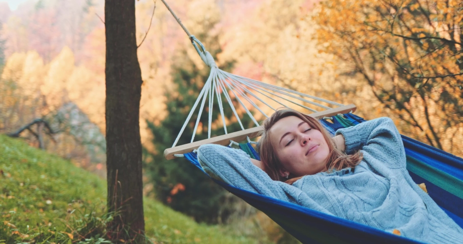 Woman Wakes Up after Sleep in a Hammock in Autumn. SLOW MOTION. Young woman daydreams, unwinds in a calm fall outdoor, rural country nature with colourful forest in background. Cozy season. | Shutterstock HD Video #1037683004