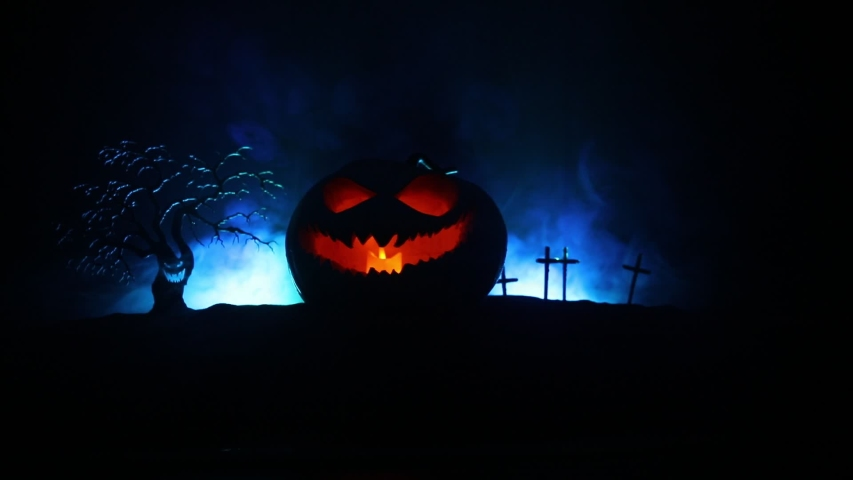 Halloween pumpkin smile and scary eyes for party night. Close up view of scary Halloween pumpkin with eyes glowing inside at black background. Selective focus | Shutterstock HD Video #1037686496