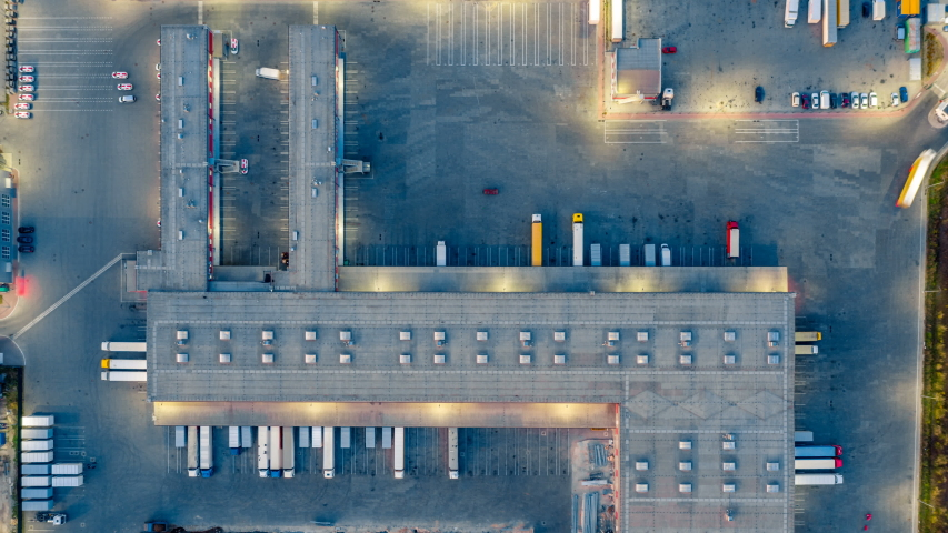 Aerial top view of the large logistics park with warehouse, loading hub with many semi-trailers trucks standing at the ramps for load/unload goods at night. Hyper lapse (time lapse) | Shutterstock HD Video #1037690000