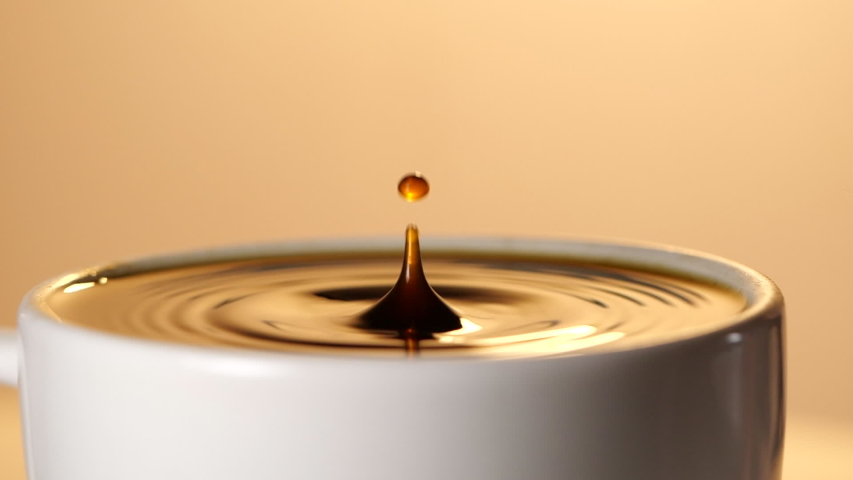 Espresso coffee drop into the filled Cup from the coffee machine in slow motion #1037692046