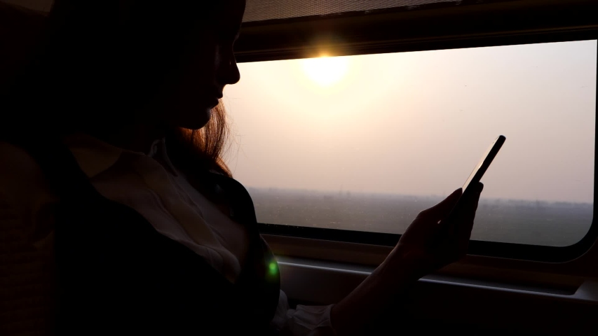 Passenger woman sit against window of high speed Chinese train, look to smartphone, slow motion. Bullet train rush at Shanghai-Beijing route at evening time, bright sun shine outside, silhouetted shot
