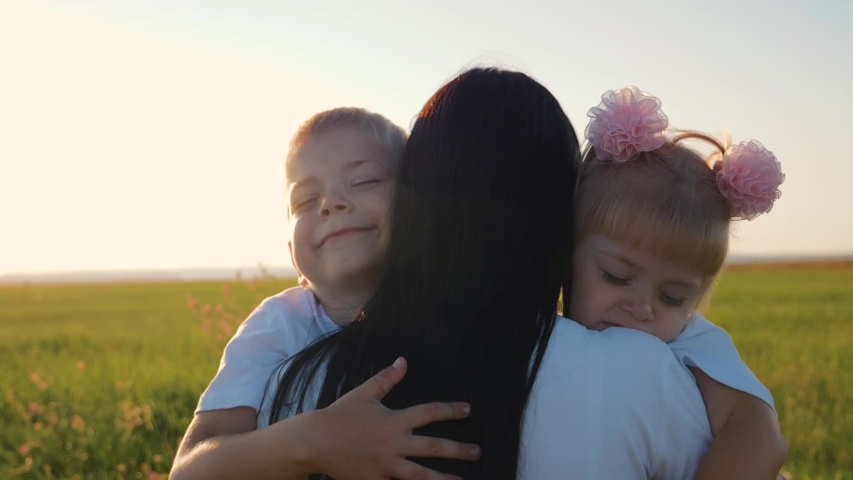 A happy family. A young mother hugs her two young children, laughing in a field in the sun at sunset. Family love concept | Shutterstock HD Video #1037701319