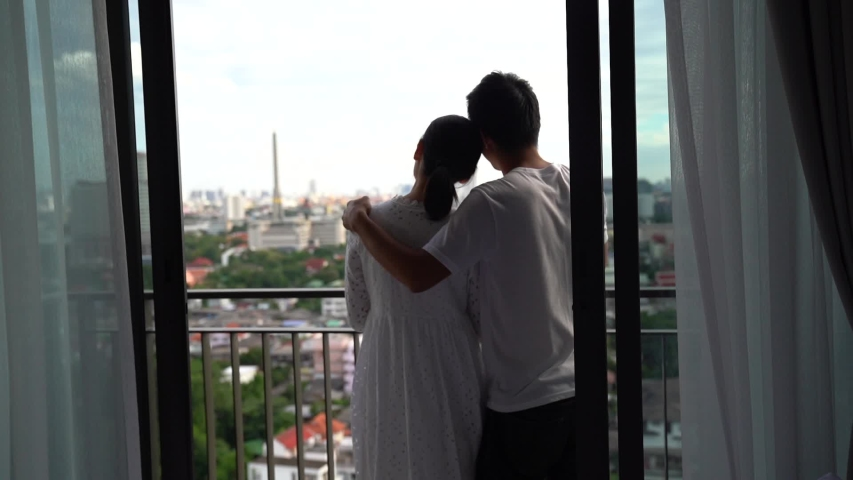 Beautiful young Asian couple spending time together on balcony with city views, Urban condominium.