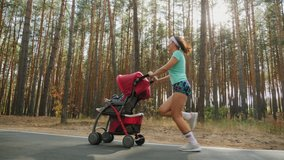 Running American girl with baby stroller enjoying a sunny summer day in a pine forest. Jogging or power walking, active family with baby jogger. Slow-motion 4k video