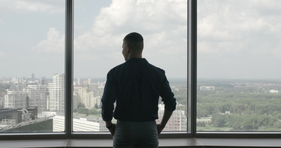 Back view of young businessman standing in a modern office, near panoramic window, man looks at the city. #1037710253