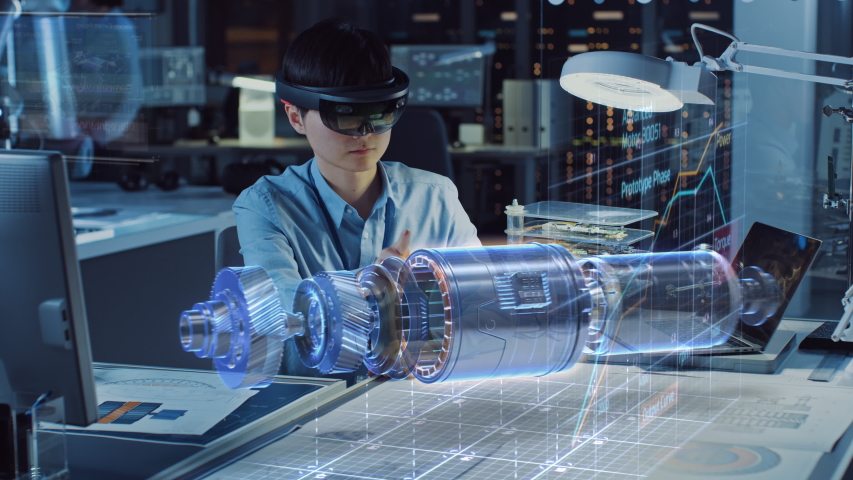 Industrial Factory Chief Engineer Wearing AR Headset Designs a Prototype of an Electric Motor on the Holographic Smart Blueprint. Futuristic Virtual Design of Mixed Technology Application.