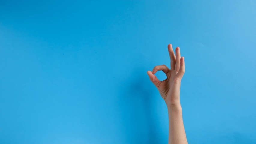 Unrecognizable female shows an ok sign on wall blue background.  Hand sign. Body language and meditation concept. With place for text or image, promotional content. | Shutterstock HD Video #1037717435