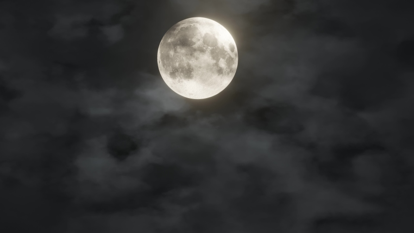 Full glowing yellow moon with clouds being blown by winds during storm at nights. Element of this footage furnished by NASA Royalty-Free Stock Footage #1037728922