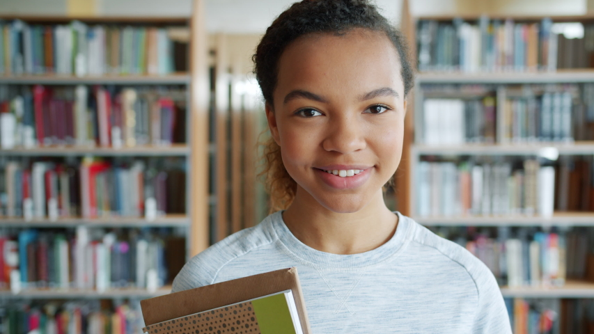 Portrait of attractive African American girl student holding books in high school library smiling looking at camera. Education, literature and people concept.