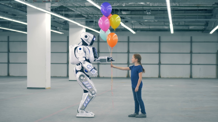 Little girl gifts balloons to a robot, side view. School kid, education, science class concept. | Shutterstock HD Video #1037737892