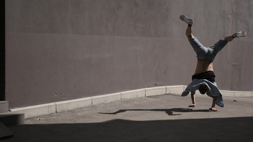 Street break dance. Young male dancer dancing various dance moves freestyle. Talented young man performing cool dance against the wall. Urban dancing freestyle in the city