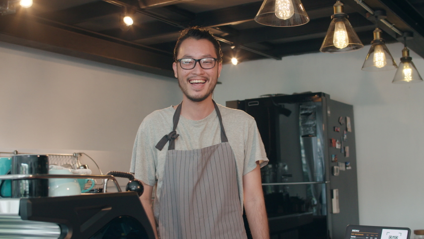 Portrait young Asian man barista feeling happy smiling at urban cafe. Small business owner Japanese male in apron relax toothy smile looking to camera standing at the counter in coffee shop.