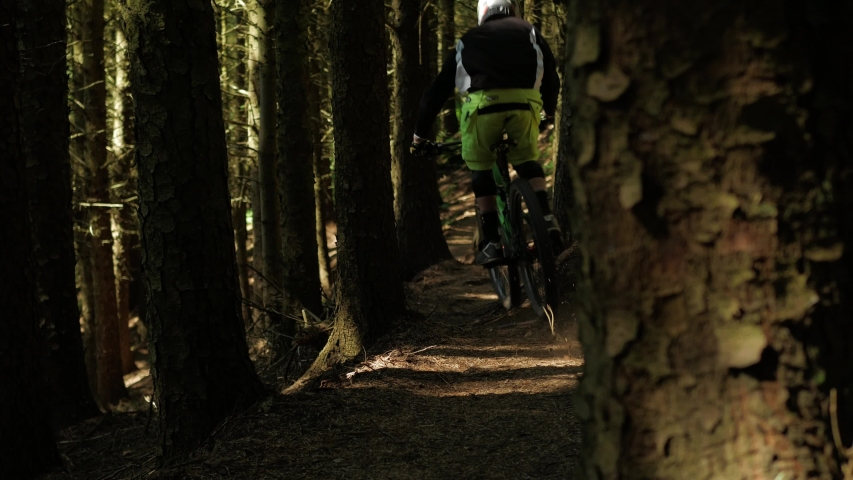 Barnstaple / United Kingdom (UK) - 05 20 2019: Mountain bike professional drives at high speed through the forest on narrow paths. Dangerous sport.