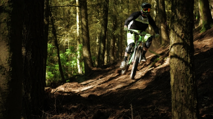 Barnstaple / United Kingdom (UK) - 05 20 2019: Mountain bike professional drives at high speed through the forest and brakes sharply and looks into the camera. Close Up Shot.