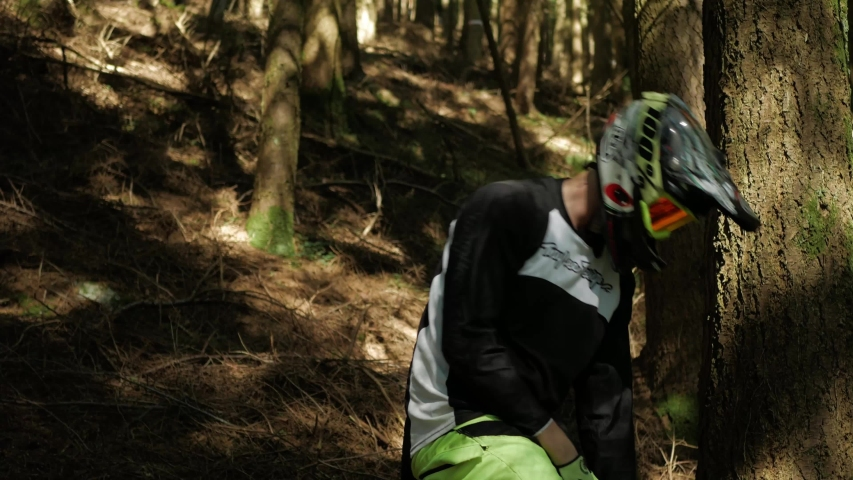 Barnstaple / United Kingdom (UK) - 05 20 2019: Professional Mountain biker pushes his bike up the mountain. Close Up Shot