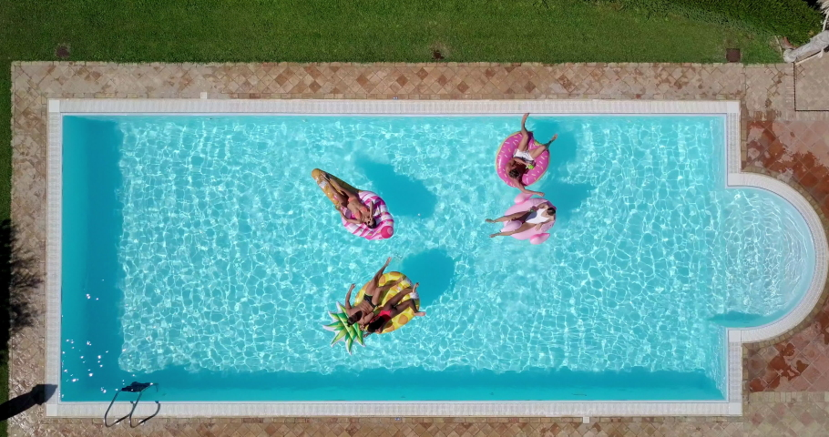 Aerial shot of young multi-ethnic friends in swimwear are relaxing in swimming pool with colorful inflatables in a sunny day. | Shutterstock HD Video #1037773469