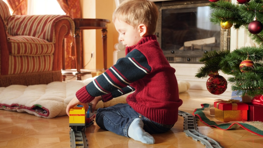 4k video of little toddler boy building toy train and railroad from bricks and blocks under Christmas tree. Child receiving gifts and presents from Santa Claus on winter holidays and celebrations #1037774693
