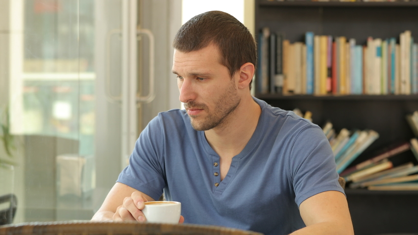 Sad man complaining holding coffee cup sitting in a restaurant