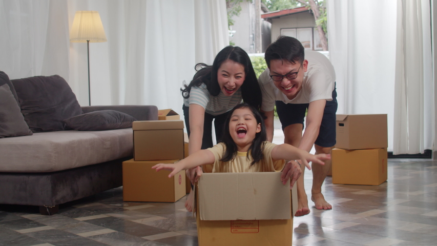 Happy Asian young family having fun laughing moving into new home. Japanese parents mother and father smiling helping excited girl riding in cardboard box. New property and relocation. Slow motion. Royalty-Free Stock Footage #1037781935