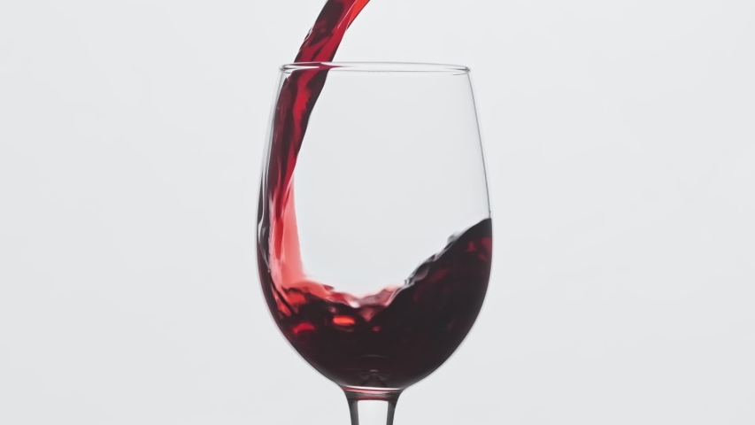 Red wine forms beautiful wave. Wine pouring in wine glass over white background. Close-up shot. Slow motion of pouring red wine from bottle into goblet. | Shutterstock HD Video #1037783906