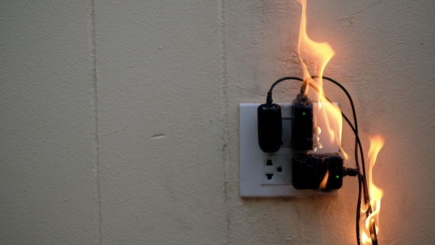 On fire adapter at plug Receptacle on white background, Electric short circuit failure resulting in electricity wire burnt