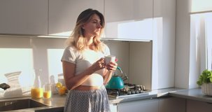Pretty Caucasian young woman in pajama standing in the sunny kitchen in the morning, drinking hot coffe or tea and enjoying her time. Stay at home, quarantine, pandemic, coronavirus ,virus