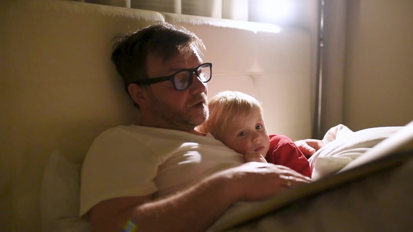 Father reading bedtime stories to child. Dad putting son to sleep. Quality family time.