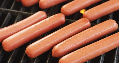 Video Slide Across Delicious Uncooked Hot Dogs Cooking On A Grill