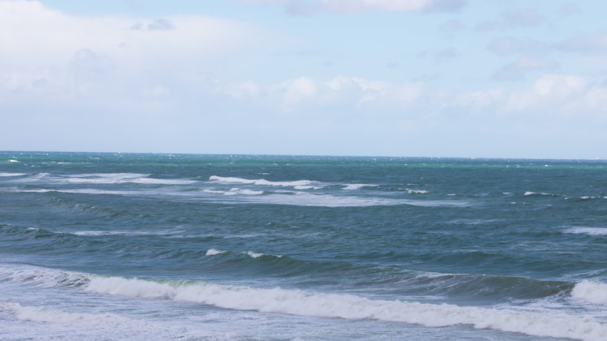 A steady wide shot of the boundless horizon and the frothy tides of the turquoise-colored ocean water. | Shutterstock HD Video #1037814167