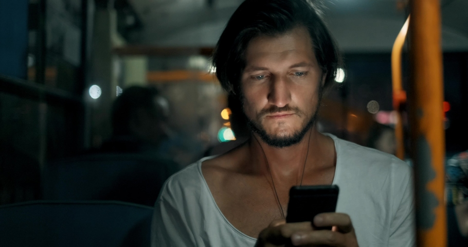 Young man holds smartphone and smiling while traveling by bus at night. Bearded male in headphones with phone, touches screen with fingers and looks out window
