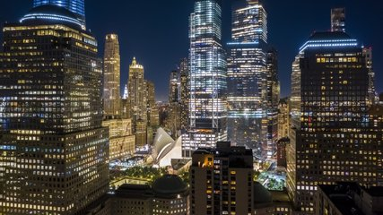 Aerial drone hyperlapse of New York skyline at night with pull back motion away from the Lower Manhattan skyscrapers