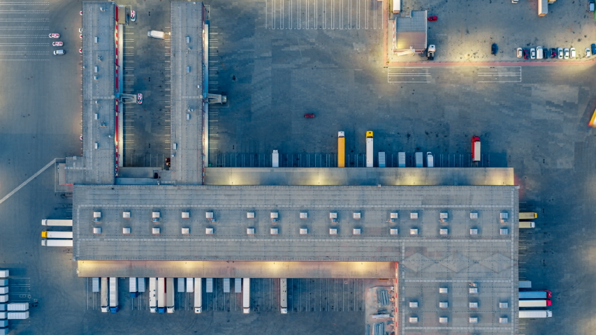 Aerial top view of the large logistics park with warehouse, loading hub with many semi-trailers trucks standing at the ramps for load/unload goods at night. Hyper lapse (hyperlapse - time lapse)