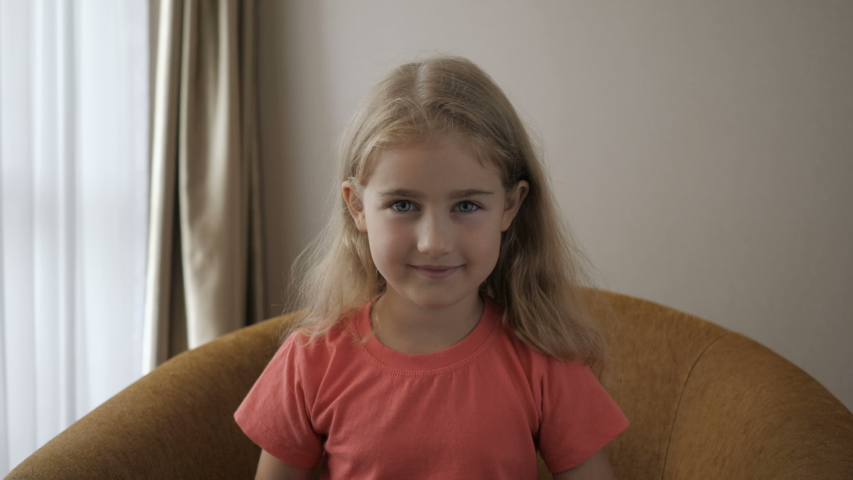Happy Cute Little Vlogger Saying Hello Hi Looking At Camera Talking To Webcam. Kid Child Girl Making Online Video Call Recording Vlog Sitting On Sofa , Portrait. Funny Girl Smiling Looking At Camera.
