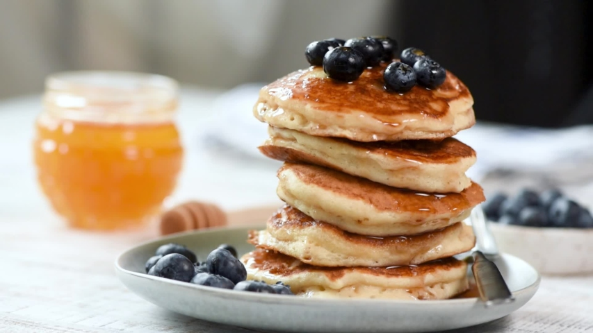 Pancakes stack with blueberries and honey on table. Tasty healthy breakfast. Fluffy american buttermilk pancakes Royalty-Free Stock Footage #1037825618