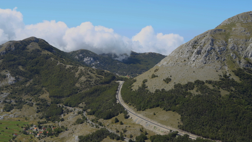 Time lapse. Montenegro, National park Lovcen. Clouds float over the mountain peaks, drive on road. Beautiful landscape. | Shutterstock HD Video #1037828492