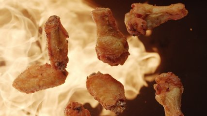 Top view of fried chicken wings flying upwards with blazing fire. Slow motion video on black background