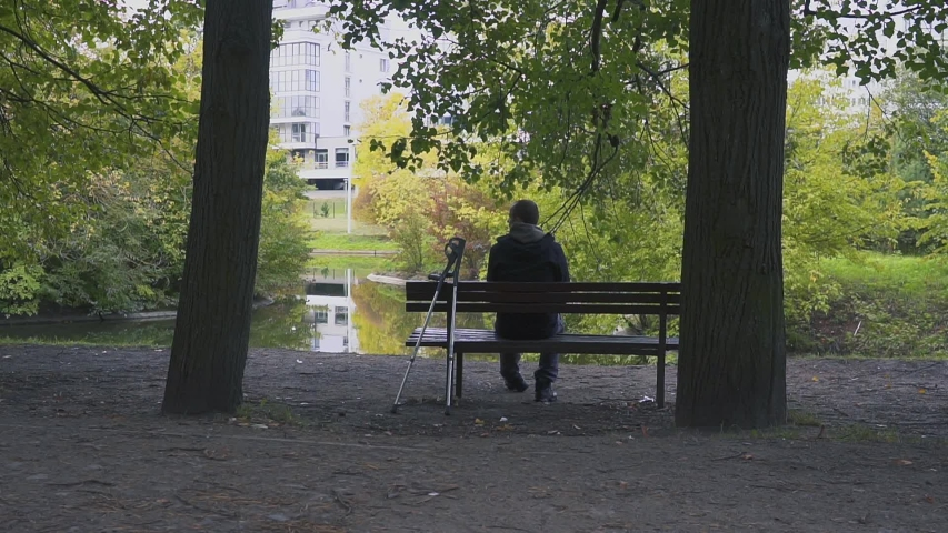 Injured Man with crutches sitting on a bench in the autumn Park
