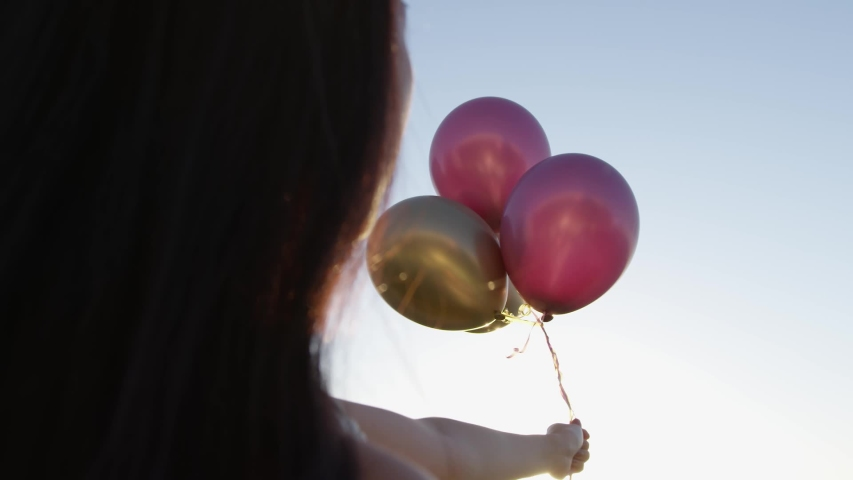 Over the shoulder of Japanese girl holding gold and pink balloons from a rooftop party at sunset, sky background. Slow Motion. Shot on Red Camera. | Shutterstock HD Video #1037832779