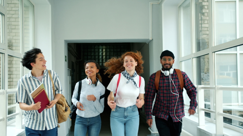 Happy friends girls and guys are running in school hallway doing high-five laughing jumping holding books. People, lifestyle and positive emotions concept.