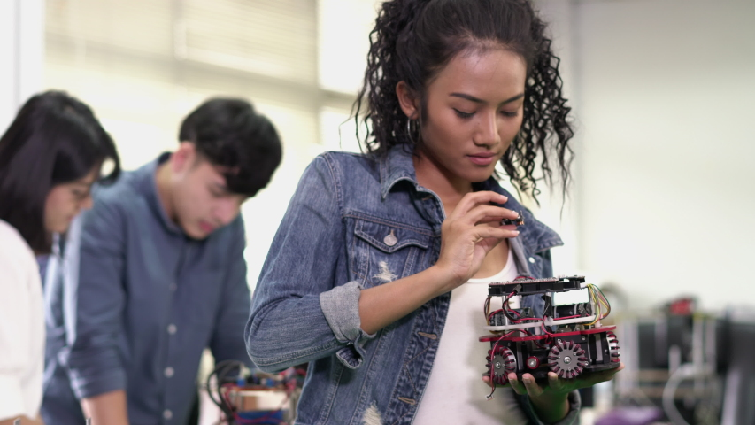 Asian young engineer students are assembling and testing electric robotics arm in modern laboratory. Concept of configuration, technological developments and innovation. | Shutterstock HD Video #1037842811