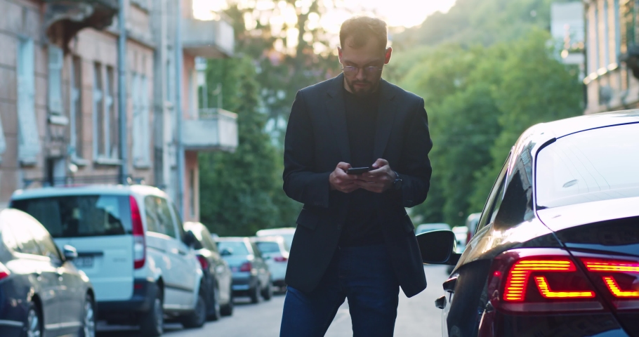 Young caucasian man business guy arriving home parking modern black car browsing on smartphone at sunset outdoors.