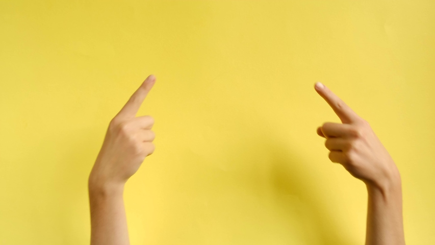 Female hands pointing on copyspace isolated over yellow background in studio. Body language concept. With place for text or image, promotional content. Advertising area, workspace mock up | Shutterstock HD Video #1037854736