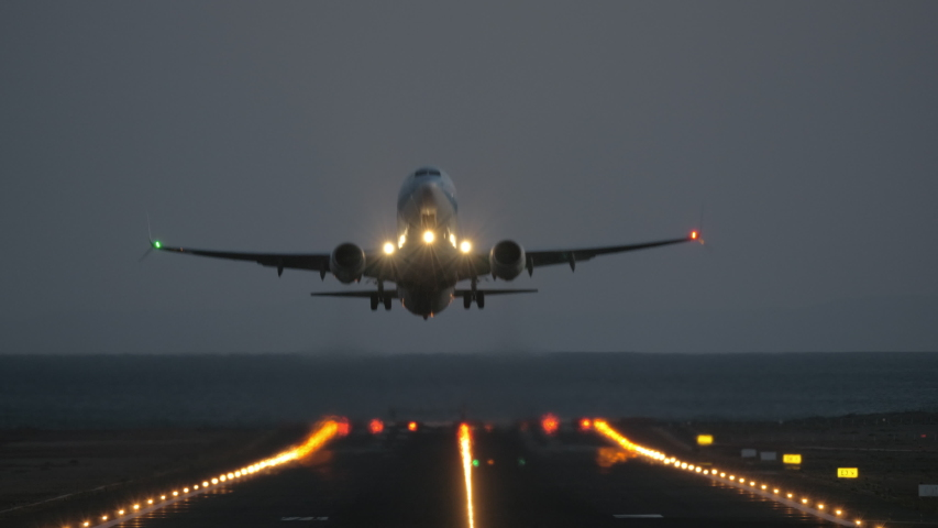 A frontal takeoff at night - we see an illuminated airstrip and a blinking plane, riding to the camera and finally taking off | Shutterstock HD Video #1037860103