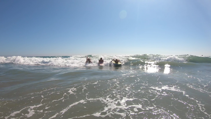 3 Young women riding a wave on boogie boards in the ocean as they have fun and laugh.   Shutterstock HD Video #1037866892
