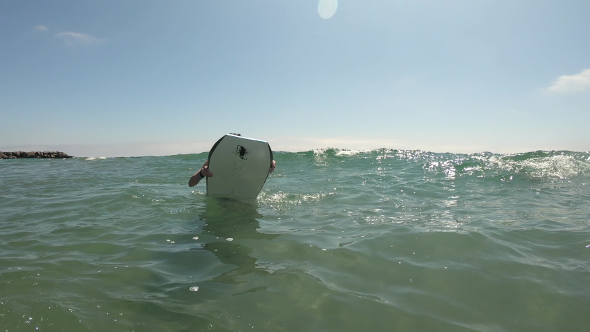 Young man paddling as he jumps in front of wave on boogie board to ride it into shore.   Shutterstock HD Video #1037866949