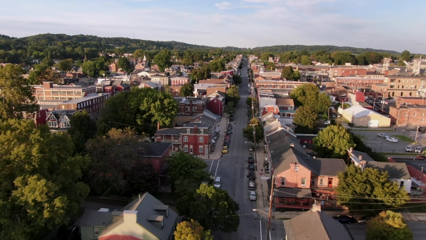 Cinematic drone aerial tracking street in small town America neighborhood community at sunset