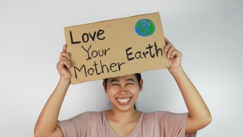 """Woman holding """"Love your Mother Earth"""" Poster on a demonstration due to climate change by plastic pollution. 