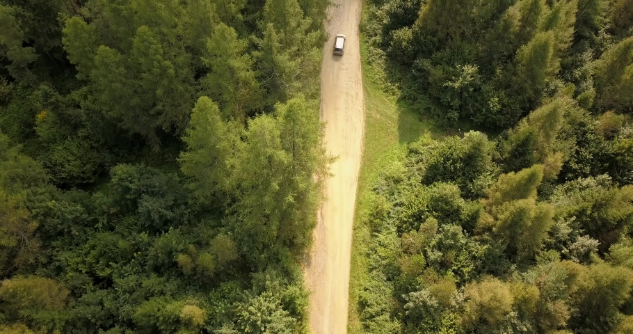 Aerial view of car driving on country road in forest and mountains. Car driving along #1037875043