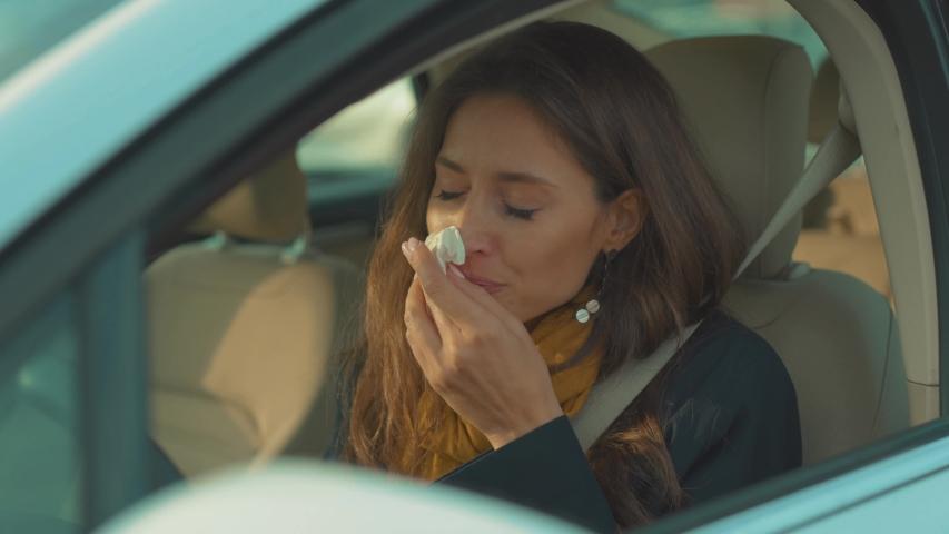 Young woman sitting in car feesneeze holds a handkerchief sick seat belt fastens vehicle influenza health illness flu medical sickness problem business infection headache slow motion | Shutterstock HD Video #1037883386