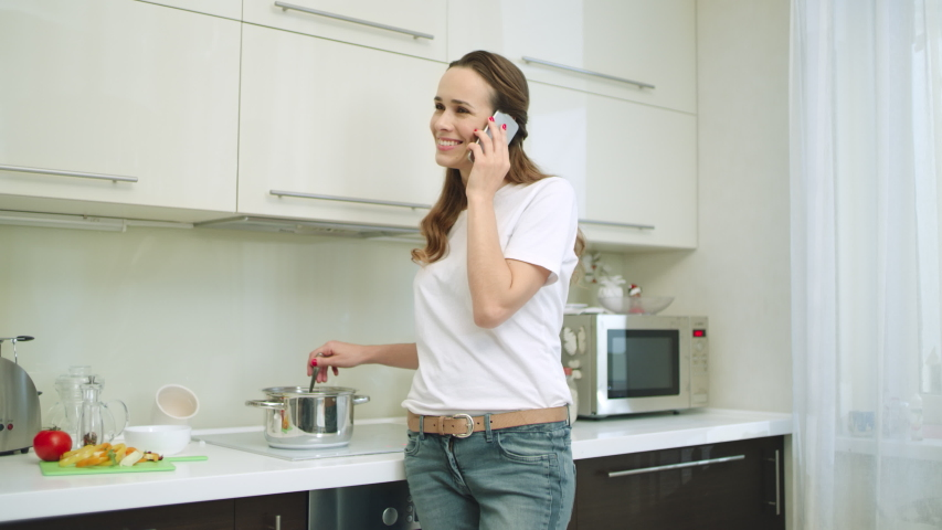 Beautiful woman talking mobile phone at luxury home. Smiling girl calling phone at kitchen. Happy woman cooking healthy dinner at modern kitchen. #1037884724